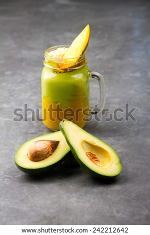 Fresh avocado and mango smoothie on a gray vintage table - stock photo