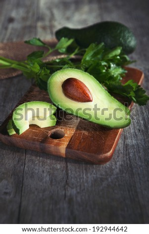 Fresh avocado on cutting board on old wooden background  - stock photo