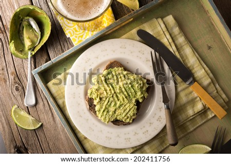 Fresh avocado on toast -  the perfect lunch or snack. Served with beer. - stock photo