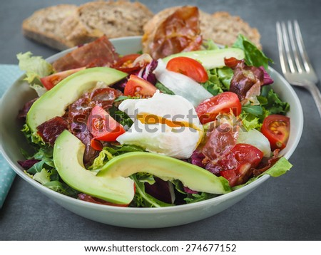 Fresh avocado salad with lettuce, tomatoes, ham and pouched egg, covered with herbal dressing