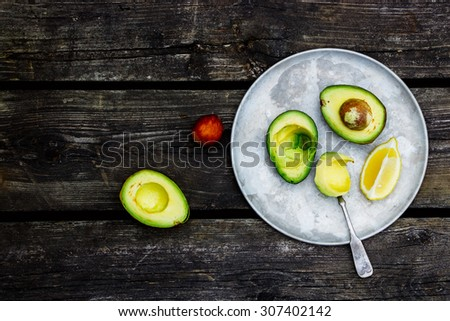 Fresh avocados on vintage metal plate over rustic wooden background with space for text. Top view. Food or cooking concept. - stock photo