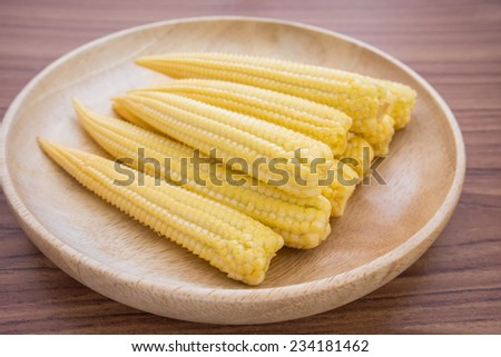 Fresh baby corn on wooden plate - stock photo