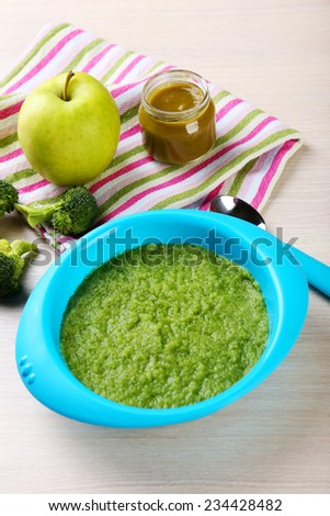 Fresh baby food in bowl with spoon - stock photo