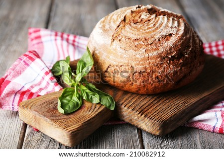 Fresh baked bread and fresh basil on cutting board, on wooden background - stock photo