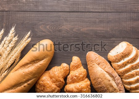 Fresh baked bread and wheat on wooden background. - stock photo