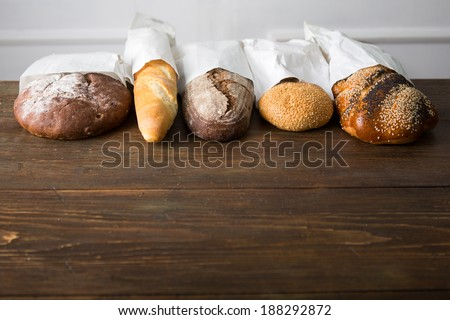 Fresh baked bread at wooden table - stock photo