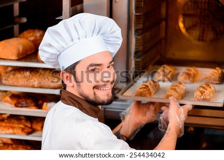 Fresh baked bread. Confident young man in apron taking the fresh baked bread from oven and looking over his shoulder with a smile in the bakery shop  - stock photo