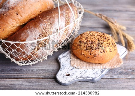 Fresh baked bread in basket, on wooden background - stock photo