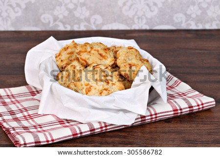 Fresh baked cheddar, garlic biscuits in a napkin lined basket.  Selective focus on front biscuit. - stock photo