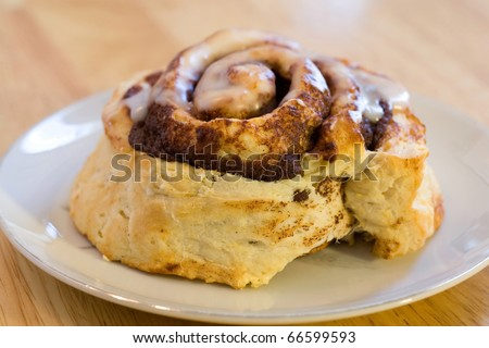 Fresh baked cinnamon roll iced and on white plate
