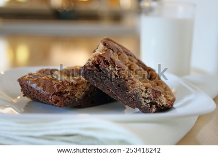 Fresh baked cookie brownies on a plate with glass of milk in background. - stock photo