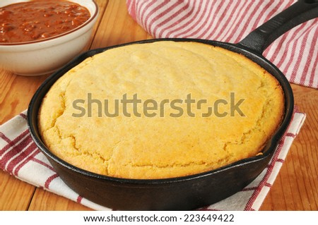 Fresh baked cornbread in a cast iron skillet with a bowl of chili - stock photo