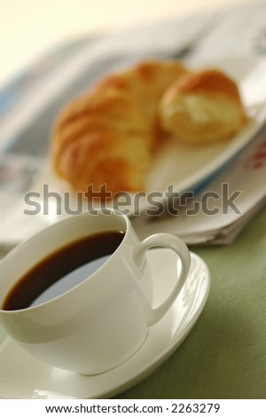 Fresh-baked croissant, cup of coffee and newspaper. Shallow DOF. Focus on cup. - stock photo