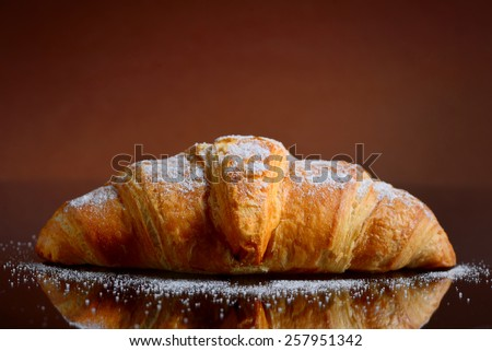 Fresh baked croissant with sugar - stock photo
