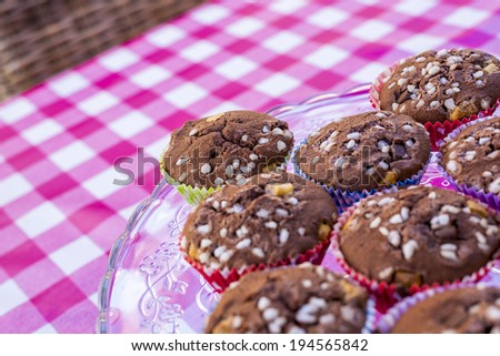 fresh baked cupcakes on glass dish, shallow depth of field - stock photo