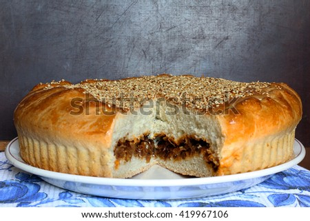 Fresh baked flavored homemade round cabbage pie with cutting out section, sliced, portion on the dark brown wooden background, just from oven, selective focus, close up - stock photo