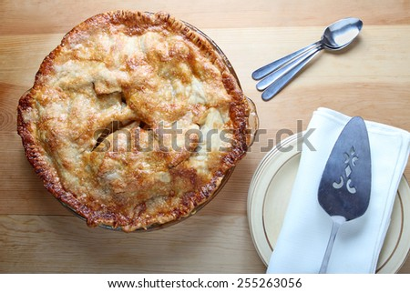 Fresh baked homemade apple pie with pie server, plates, and spoons. - stock photo