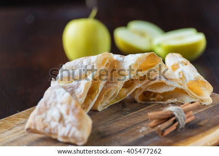 fresh baked homemade apple strudel on kitchen table with apples. Rustic style. Natural day light - stock photo