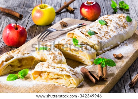 fresh baked homemade apple strudel with powdered sugar and mint leaves. - stock photo