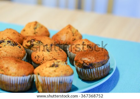 Fresh baked muffins on a blue plate - stock photo