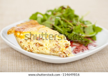 Fresh baked slice of quiche lorraine on a plate - stock photo