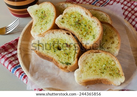 Fresh baked sliced garlic bread on a wooden plate - stock photo