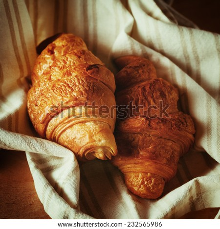 Fresh baked tasty croissant with chocolate close up. Instagram color effect. - stock photo