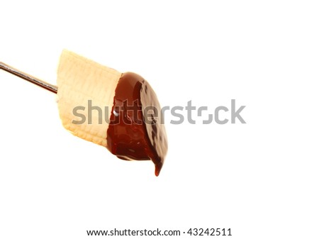 Fresh banana with dark chocolate sauce dripping from it - stock photo