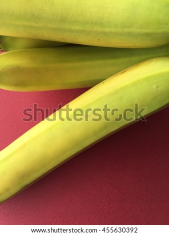 Fresh bananas on dark red with copy space