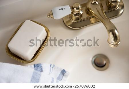 Fresh Bar of Artisan Soap Next to Brass Vintage Sink - stock photo