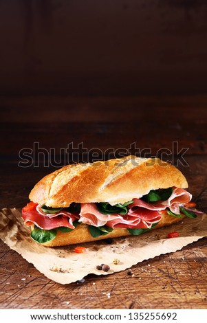 Fresh basil and thinly sliced cold ham on a crusty freshly baked baguette on a sheet of crumpled paper - stock photo