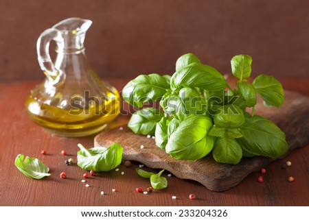 fresh basil leaves herb and olive oil on wooden background - stock photo