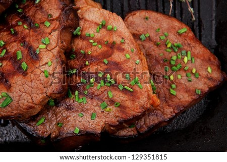 fresh bbq red meat with thyme and cayenne pepper on barbecue pan isolated on white background