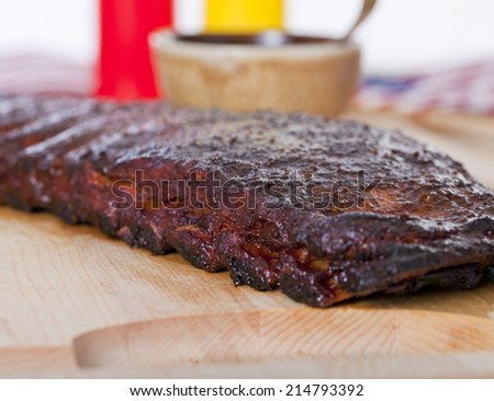 Fresh BBQ ribs on a wooden chopping board in studio