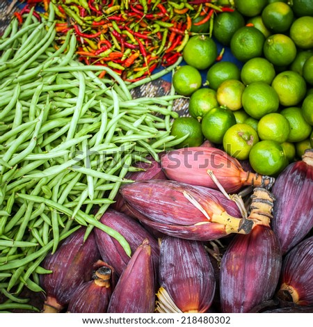 Fresh beans, banana flowers, lime and chili peppers for sale at asian market. Organic food background - stock photo