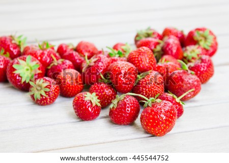Fresh beautiful strawberries in the shape of a heart on a white wooden table. . Natural strawberry from the fruit garden. - stock photo