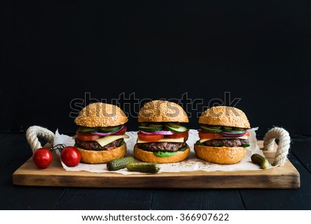 Fresh beef burgers with cheese, vegetables, pickles and spicy tomato sauce on paper over rustic wooden tray, black background, copy space - stock photo