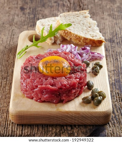fresh beef tartar with egg on wooden cutting board - stock photo