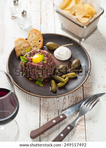 Fresh beef tartare with egg, cucumber and onion, selective focus - stock photo