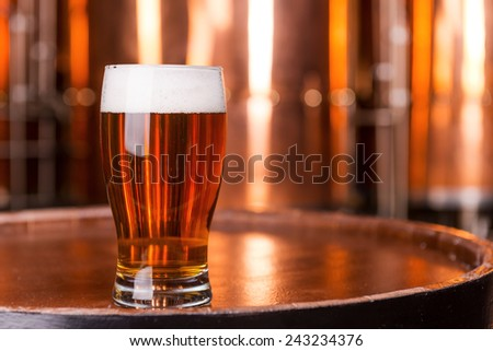 Fresh beer. Close-up of glass with beer standing on the wooden barrel with metal containers in the background - stock photo