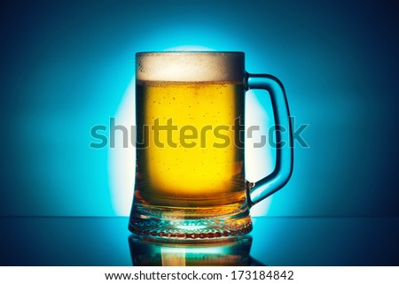fresh beer on blue background - stock photo