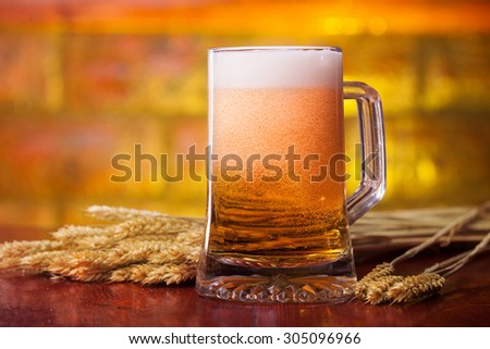 Fresh beer on the wooden table  - stock photo