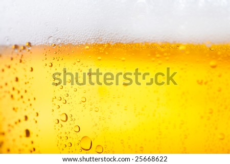 Fresh beer with froth and condensed water pearls - stock photo
