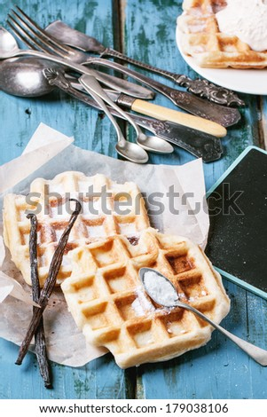 Fresh belgian waffles served with vanilla sticks and vintage cutlery over blue wooden table. See series - stock photo