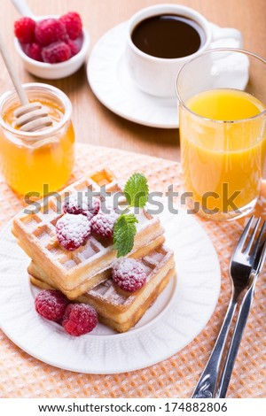 Fresh Belgian waffles with raspberries, honey and cup of coffee - stock photo