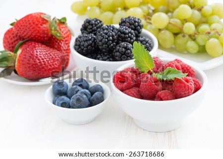Fresh berries and grapes on a white wooden table, close-up, horizontal - stock photo