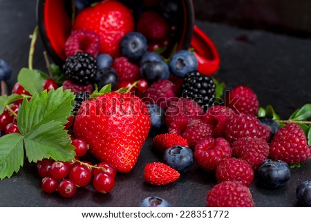 fresh  berries falling out of red mug  on black  background, low key - stock photo