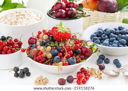 fresh berries, fruit, cereal and milk for breakfast, close-up - stock photo