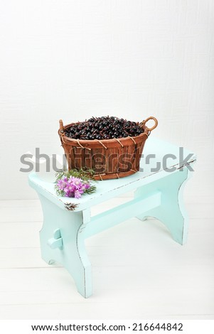 Fresh berries in basket on white wall background - stock photo