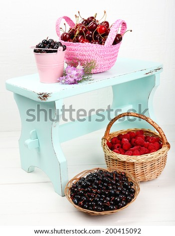 Fresh berries in baskets on white wall background - stock photo